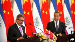 El Salvador's Foreign Minister Carlos Castaneda, left, speaks as China's Foreign Minister Wang Yi listens at a signing ceremony to mark the establishment of diplomatic relations between El Salvador and China at the Diaoyutai State Guesthouse in Beijing, Aug. 21, 2018.