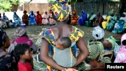 A mother carrying an infant on her back attends a meeting of women in Diabougo, Senegal.