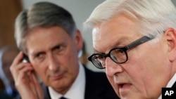 Los ministros de Relaciones Exteriores de Alemania, Frank-Walter Steinmeier, derecha, y Gran Bretaña, Philip Hammond colaborarán con envío de armas y suministros mas no atacarán.