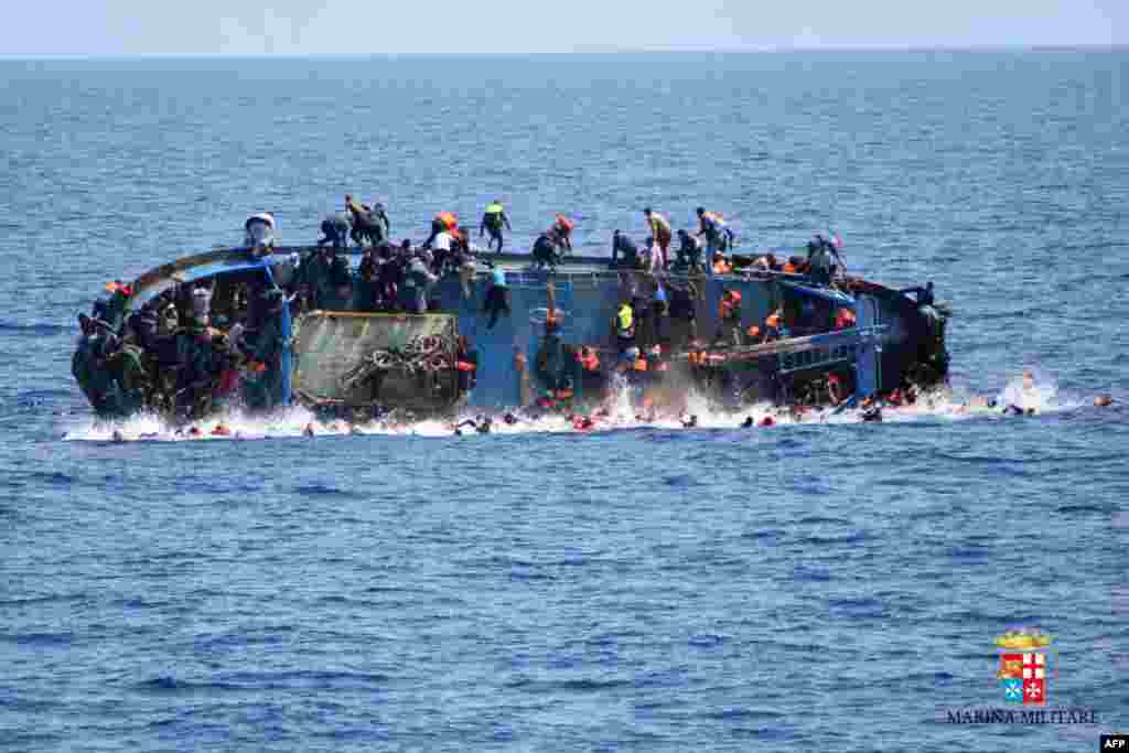 This handout picture by the Italian Navy (Marina Militare) shows the shipwreck of an overcrowded boat of migrants off the Libyan coast. At least seven migrants have drowned after the overcrowded boat overturned, the Italian Navy said. Five hundred people were pulled to safety, but rescue operations were continuing and the death toll could rise, the navy said.