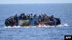 Cette image fournie par la marine italienne montre le naufrage d'une embarcation surpeuplée de migrants au large des côtes libyennes, mercredi 25 mai 2016.