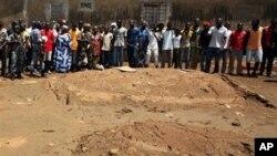 Les habitants de Yopugon observant les forces républicaines, lors d'une visite d'un lieu qui pourrait cacher un charnier le 5 mai 2011