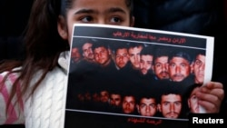 A girl holds up a poster with pictures of the 21 Egyptian Coptic Christians beheaded by Islamic State in Libya as protesters gather in a gesture to show their solidarity in front of the Egyptian Embassy in Amman, February 17, 2015.