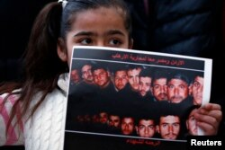 A girl holds up a poster with pictures of the 21 Egyptian Coptic Christians beheaded by Islamic State in Libya, as they gather in a gesture to show their solidarity, in front of the Egyptian embassy in Amman, February 17, 2015.