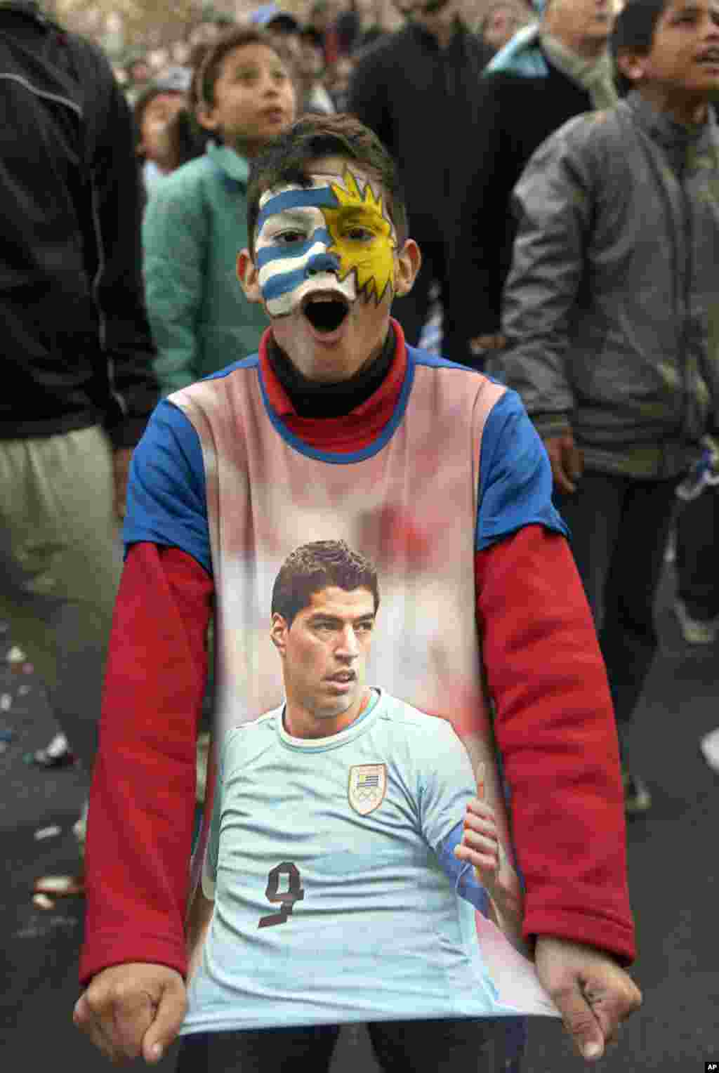 A fan, with his face painted to represent his country's flag and wearing a T-shirt with an image of Uruguayan footballer Luis Suarez, cheers as he watches a live broadcast of the World Cup match between England and Uruguay in downtown Montevideo, Uruguay,