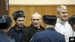 Mikhail Khodorkovsky, center, and his co-defendant Platon Lebedev, right, are escorted to a court room in Moscow, 27 Dec 2010