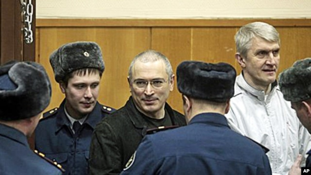 Mikhail Khodorkovsky, center, and his co-defendant Platon Lebedev, right, are escorted to a court room in Moscow, 27 Dec 2010.