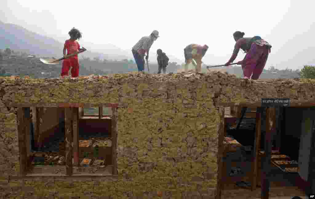 A family works to rebuild their damaged house in Lalitpur, Nepal. The April 25 earthquake killed thousands and injured many more as it destroyed mountain villages and buildings and archaeological sites in Kathmandu.