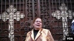 Seorang jemaah gereja menangis di depan Gereja Kristen Koptik di Alexandria yang dikoyak pada malam Tahun Baru.