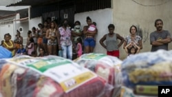 Residents wait for donated food from a campaign organized by state-run oil company Petrobras workers and the oil workers union, amid the new coronavirus pandemic, in the Vila Vintem favela in Rio de Janeiro, Brazil, Friday, Oct. 16, 2020. (AP Photo/Bruna