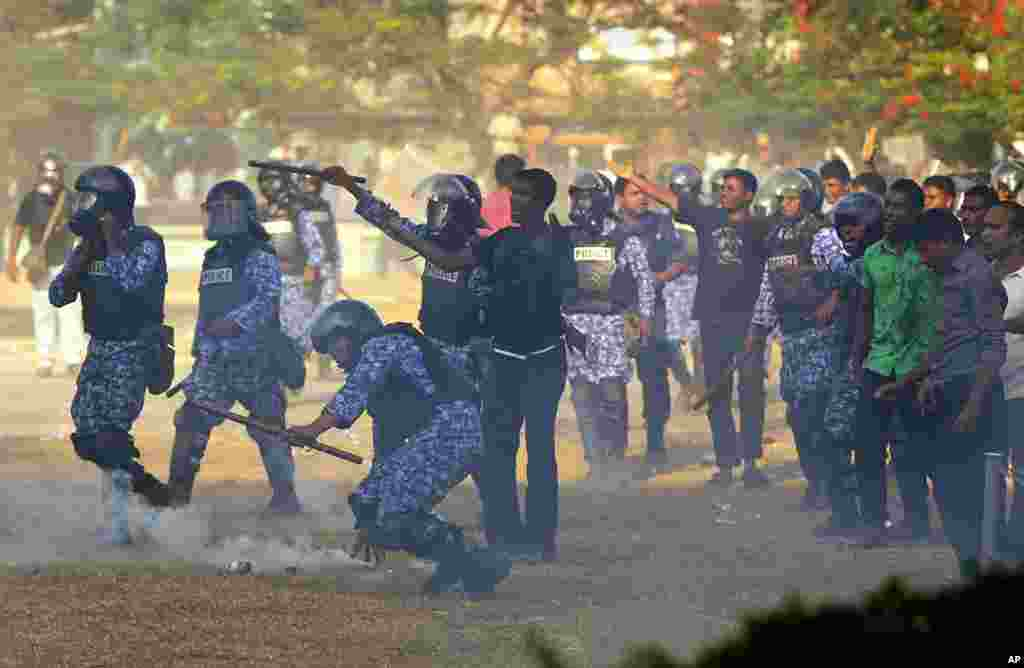 Maldives police officers throw tear gas canisters during a clash with the military in Male, Maldives, February 7, 2012. (AP)