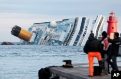 FILE - The cruise ship Costa Concordia lays on its side off the tiny Tuscan island of Giglio, Italy, Jan. 18, 2012.