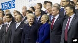US Secretary of State Hillary Rodham Clinton, center, is flanked by Lithuania's FM Audronius Azubalis, right, and Lithuania's President Dalia Grybauskaite, left, as they attend an international conference of the Organization for Security and Cooperation i