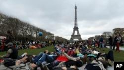សកម្មជនធ្វើឈុតសម្តែងជាស្លាប់ នៅក្នុងបាតុកម្មមួយនៅជិត Eiffel Tower នៅក្រុងប៉ារីសនៅអំឡុងពេលកិច្ចប្រជុំអាកាសធាតុអង្គការសហប្រជាជាតិនៅថ្ងៃទី១២ ខែធ្នូ ឆ្នាំ២០១៥។