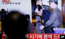 FILE - A man watches a live TV news program showing North Korean leader Kim Jong Un's uncle Jang Song Thaek, second from right, being escorted by military officers during a trial in Pyongyang, North Korea, Dec. 12, 2013.