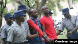 FILE - Activist Itai Dzamara, center left in red and blue, is detained by police in Zimbabwe in this undated photo and has been missing since 2015.