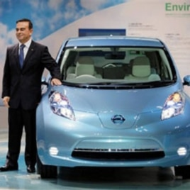 Nissan chief Carlos Ghosn stands next to a Nissan Leaf, a fully electric car