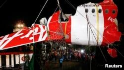 Bagian ekor pesawat AirAsia QZ8501 diangkat dari kapal ke truk di Pelabuhan Kumai, dekat Pangkalan Bun, Kalimantan Tengah (11/1). (Reuters/Darren Whiteside)