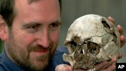 FILE - Dr. Chris Stringer the principal researcher of human origin at the Natural History Museum in London with the skull of Cheddar Man, a 9,000-year-old skeleton, March 7, 1997. (AP Photo/Michael Stephens)