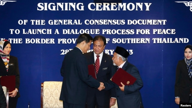 Secretary-General of Thailand's National Security Council, Paradorn Pattanathabutr, center left, shakes hands with chief of Thailand's National Revolution Front (BRN) liaison office in Malaysia, Hassan Taib, center right, Kuala Lumpur, Feb. 28, 2013.