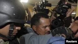 Rubén Villalba, presunto líder de un movimiento de campesinos sin tierra que se enfrentaron con la policía en junio, es escoltado por la policía tras su captura en Asunción. Su abogado, Luis Casabianca presentó un hábeas corpus para que lo liberen.