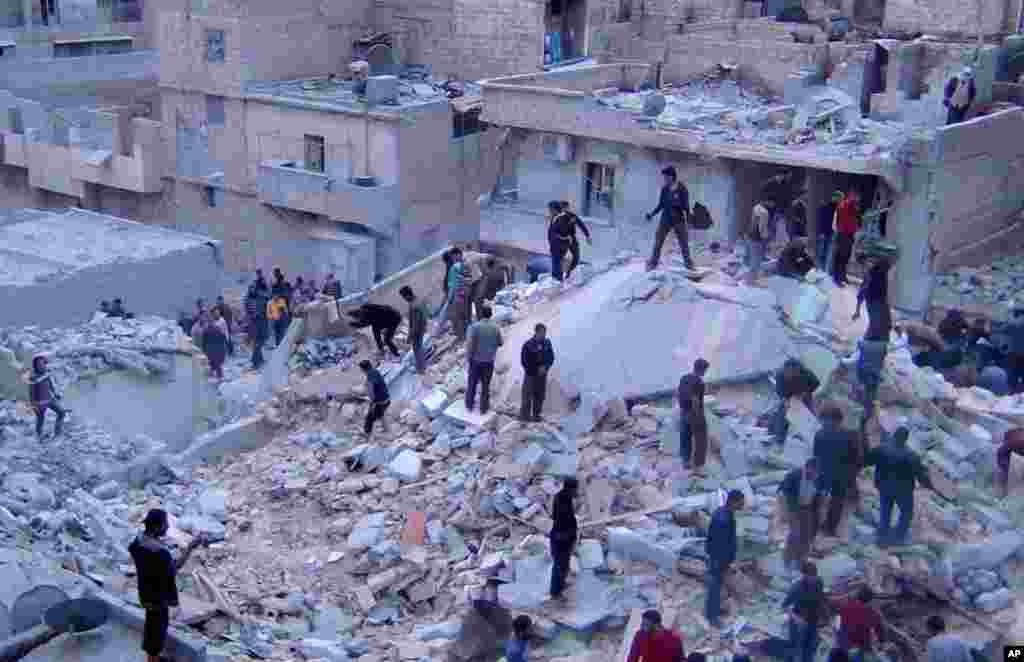 This citizen journalism image provided by the Aleppo Media Center shows Syrians searching for dead bodies in the rubble of buildings hit by Syrian airstrikes, Aleppo, March 20, 2013.
