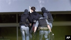 An alleged al-Qaida member, second left, is being brought to a building of the federal court in Karlsruhe, Germany, April 30, 2011