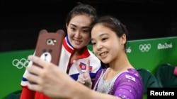 Lee Eun-Ju (KOR) of South Korea (R) takes a selfie picture with Hong Un Jong (PRK) of North Korea.