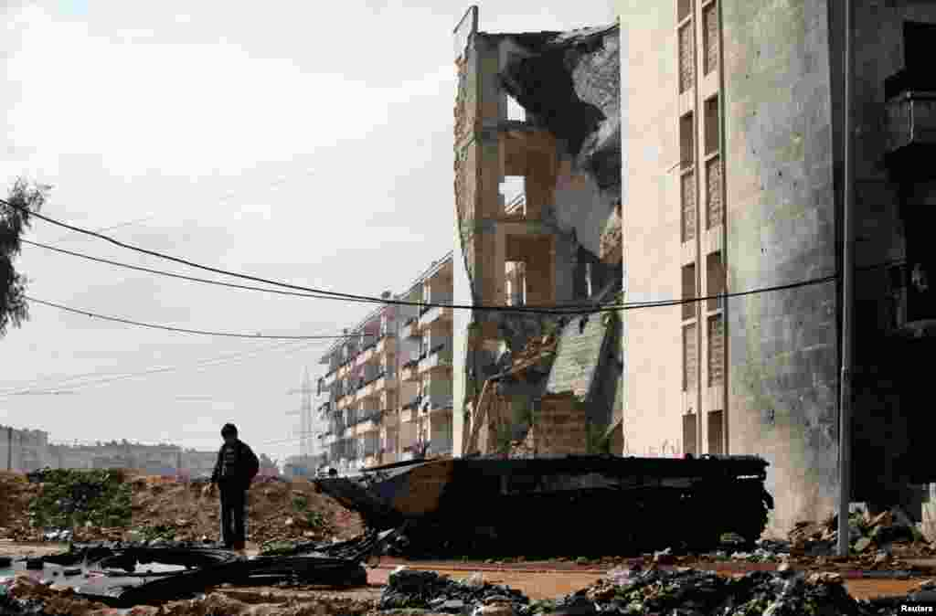 A child stands on the remnants of a destroyed military vehicle in the Al Inzarat district of Aleppo, February 17, 2013.