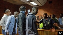Unidentified suspects are led out of court after appearing in Pretoria, South Africa, February 7, 2013.