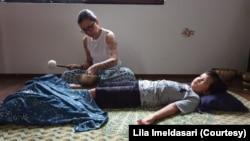 """Aksan Rana Bumi (8 tahun), penyintas kanker anak, sedang menjalani """"Singing bowl Therapy"""" bersama Janti Wignjopranoto di """"Rumah Maguwo"""" di Yogyakarta, 6 Desember 2019. (Foto: Lila Imeldasari/koleksi pribadi)"""