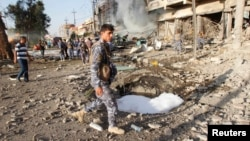 Kurdish security forces inspect the site of a car bomb attack in Kirkuk Aug. 23, 2014.