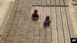 FILE - Indian children work at a brick factory on the outskirts of Jammu, May 1, 2018.