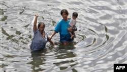 Người dân Thái Lan lội qua nước lũ ngập tới ngang hông ở Bangkok, ngày 30/10/2011
