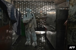 A worker wearing personal protective equipment (PPE) sprays disinfectant in the Orussey market after it was temporarily closed following a few vendors testing positive for the Covid-19 coronavirus, Phnom Penh, Cambodia, April 4, 2021. (Photo by TANG CHHIN Sothy / AFP)