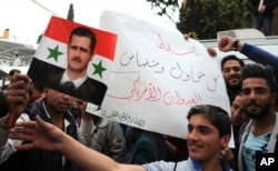 "In this photo released by the Syrian official news agency SANA, pro-government protesters hold a portrait of President Bashar Assad and a placard that reads, ""Down with everyone who cooperated and supported the American aggression,"" during a protest against the U.S. attack on a military airbase last week, in front the the U.N. building, in Damascus, April 11, 2017."
