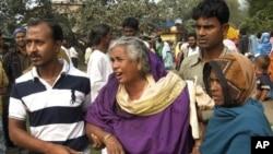 在印度﹐飲用有毒的家釀酒死亡的受害者親人在一家醫院外聚集﹐等候消息。