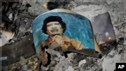 Picture of Libya's ousted leader Moammar Gadhafi among ashes in downtown Sirte, Wed., Oct. 12, 2011.