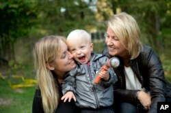 Albin's mother Emelie Eriksson, left, poses for a photo with her son and her mother Marie, right, outside her home in Bergshamra, Sweden, Sept. 20, 2016. For Emelie Eriksson, the bond she shares with her son Albin is particularly unique: both Emelie and Albin were born from the same womb, after Emelie received her mother's transplanted uterus in a revolutionary operation that links three generations of their family.