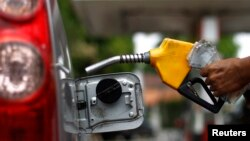 FILE - A worker fills a tank with subsidized fuel at a fuel station in Jakarta.