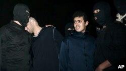 Phạm nhân Alireza Mafiha, thứ nhì từ trái, tựa đầu vào vài một nhân viên an ninh trước lúc án tử hình được thi hành,
