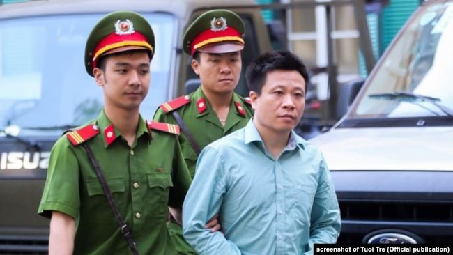 Ông Hà Văn Thắm bị dẫn vào tòa án.
