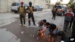Pasukan keamanan berjaga-jaga sementara para jurnalis Irak menyalakan lilin di tempat kepala biro Radio Free Iraq di Baghdad, Irak (22/3). (AP/Karim Kadim)