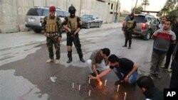 Soldados iraquís observan mientras periodistas colocan velas en el lugar en que murió el jefe de la oficina de Radio Irak libre en Bagdad.