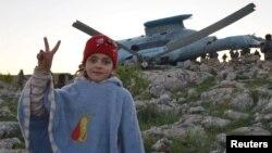 Một cô gái Syria ra dấu hiệu 'chiến thắng' bên cạnh chiếc máy bay trực thăng thuộc lực lượng trung thành của Tổng thống al-Assad bị nạn ở Jabal al-Zawiya, 22/3/15