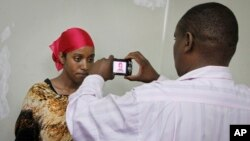 A detained Somali woman has her photograph taken before being fingerprinted and screened at the Kasarani sports stadium, which has been converted into a detention facility to hold those arrested during recent security crackdowns, near Nairobi in Kenya, April 9, 2014.