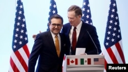 FILE - U.S. Trade Representative Robert Lighthizer embraces Mexican Economy Minister Ildefonso Guajardo during a joint news conference on the closing of the seventh round of NAFTA talks in Mexico City, March 5, 2018.