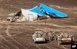Egyptian Military in cars approach a plane's tail at the wreckage of a passenger jet bound for St. Petersburg in Russia that crashed in Hassana, Egypt, on Nov. 1, 2015.