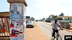 A man rides past a pillar featuring posters of the ruling party presidential candidate, incumbent President John Mahama, and opposition candidate Nana Akufo-Addo in Accra, Oct. 23, 2012.