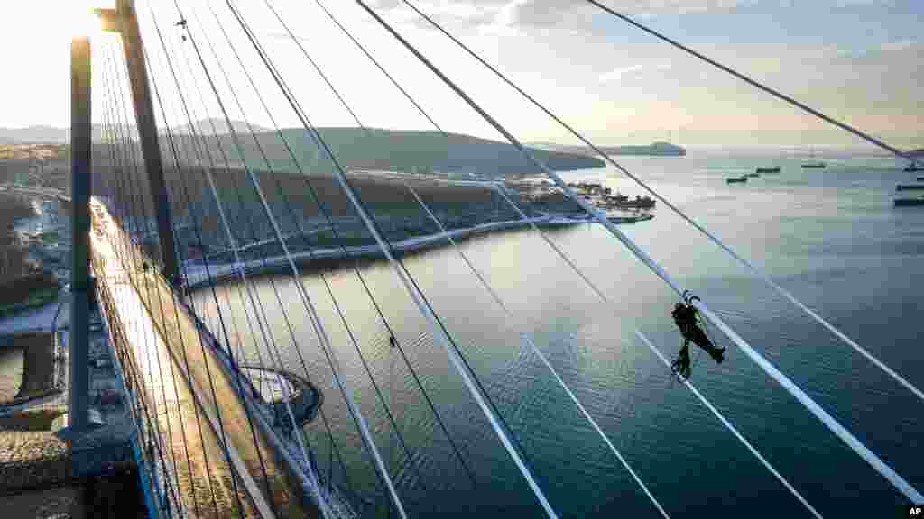 Industrial climbers remove ice from the cables of the Russky Bridge across the Eastern Bosphorus Strait in Vladivostok, Russia. The bridge was temporarily closed after an ice storm, with a ferry service between Russky Island and mainland Vladivostok.
